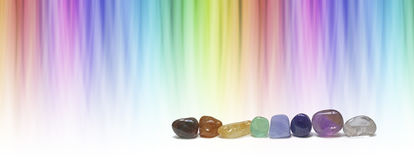 Healing chakra crystals and color healing website header. A  row of eight chakra colored tumbled crystals and against a linear graduated chakra rainbow color Stock Images