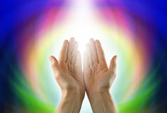 Healing Circle of Light. Healer's hands palm up with a circle of light and rainbow colors in background Stock Images