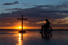 Healing Cross. Man in a wheel chair by a cross at a beach as the sunset Stock Image