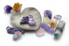 Healing Crystals. Amethyst, rose and citrine healing quartz crystals and heart shaped dish on white reflective background stock images