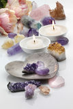 Healing Crystals. Amethyst, rose and citrine healing quartz crystals with scented candles on white reflective background royalty free stock images