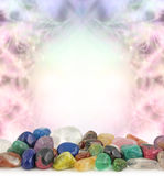 Healing Crystals Border. Decorative pastel colored border frame background with a selection of multicolored tumbled healing crystals at the front and plenty of Royalty Free Stock Photography