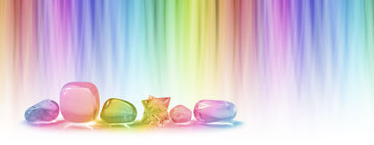Healing crystals and color healing website header. A row of five tumbled healing crystals and a merkabah against a linear graduated chakra rainbow color Royalty Free Stock Images