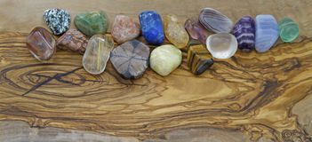 Healing crystals on olive wood background. A selection of different colored healing crystals on a flat smooth olive wood background Royalty Free Stock Image