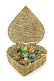 Healing crystals stored in heart shaped basket. Love heart shaped wicker basket filled with a broad selection of tumbled healing crystal gem stones with the lid Stock Photos