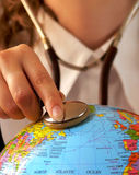 Healing the Earth. Female doctor keeping a stethoscope on a globe, symbol of the desire to heal the Earth royalty free stock image