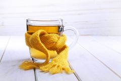 Healing glass of tea in a scarf on a wooden background.  royalty free stock photo