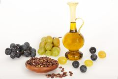 Healing grape seeds oil in a glass jar, fresh grapes on white background Stock Photo