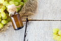 Healing grapes seeds oil in a glass jar, fresh grapes on old wooden background, seed extract has antioxidant and nourishing the sk Stock Photography