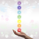 Healing Hand and seven chakras. On a sparkling pastel coloured background Stock Photo