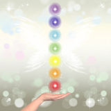 Healing Hand and seven chakras. On a sparkling pastel coloured background Royalty Free Stock Images