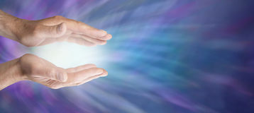 Healing hands and blue energy website banner. Male healing hands outstretched with soft white energy between on a blue energy background stock photos