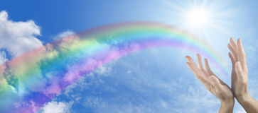 Healing hands on blue sky and rainbow banner. Website banner for a healer showing female hands cupped with rainbow arcing out on a blue sky and fluffy cloud wide Royalty Free Stock Photography