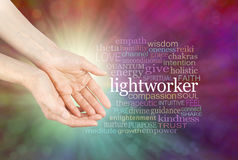 The healing hands of a Light Worker. Female hands in open gesture beside the word LIGHTWORKER and a relevant word cloud on a radiating multi-coloured bokeh Royalty Free Stock Photo