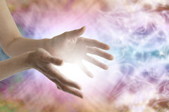 Healing Hands sending distant healing. Female hands stretched out sending distant healing with pastel colored swirling energy and light in background Stock Image