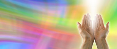 Healing Hands sending distant healing. Female hands stretched out sending distant healing with rainbow colored energy on banner background and shaft of light Stock Photos