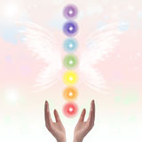 Healing Hands and seven chakras. On a sparkling pastel coloured background Royalty Free Stock Images