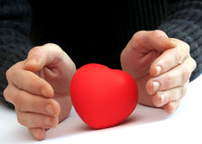 Healing the heart. Hands around a heart protecting and healing it royalty free stock photography