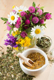 Healing herbs. Mortar with healing herbs, bouquet of daisy and clovers on wooden board, herbal medicine Royalty Free Stock Image