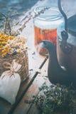 Healing herbs in basket, vintage tea kettle and jar of tea Royalty Free Stock Photography