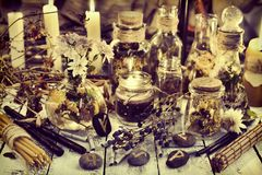 Healing herbs and berries, runes and candles on wooden table, toned image. Occult, esoteric, divination and wicca concept. Alternative medicine and homeopathic stock photography