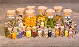Healing herbs in bottles for herbal medicine on old wooden table.  stock photos
