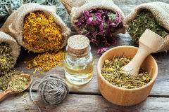 Healing herbs in hessian bags, mortar with chamomile. And essential oil on wooden table, herbal medicine Royalty Free Stock Photo