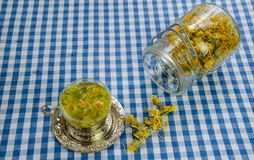 Healing marigold tea and jar dried flower on table Royalty Free Stock Photos