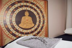 In a healing massage studio on the wall a large East Asian buddha image, in the foreground a massage table, with a white cushion,. A towel and a branch of stock photo