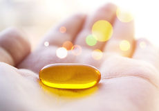 Healing pill. Cod liver oil pill in hand. Magic healing pill Stock Photos