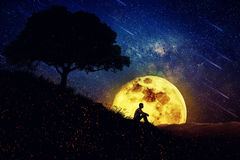 The Healing Power of Nature (Night Scene). Boy sit alone on a hill in the center of nature, over a full moon night background. Standing away from the crowd royalty free stock photo