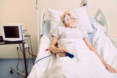 Senior woman breathing through oxygen mask at hospital. Healing process. Poor retired woman lying in a hospital bed with a drop counter and a heart rate medical stock images