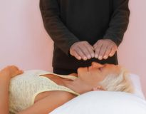 Healing session bathed in pink energy. Male healer with parallel hands hovering at waist height, channeling healing energy to happy looking female client lying Stock Images