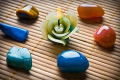 Healing stones. In circle with beautiful candle in form of flower on bamboo like a concept for alternative medicine or wellness Stock Image