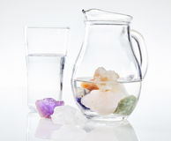 Healing stones in jug of water Stock Photography