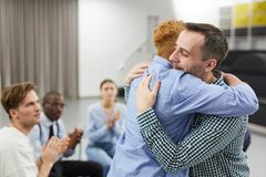Healing in Support Group. Side view  portrait of mixed race women hugging psychologist during therapy session in support group, copy space stock photos