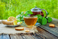 Healing tea with lemon and ginger. Tea in a glass cup on a wooden table. Folk remedy. Side view. Against green background Stock Images
