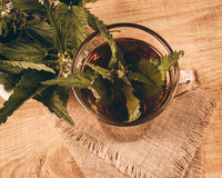 Healing tea with nettle. Tea in a glass cup on a wooden table. The source of vitamins. Royalty Free Stock Photography
