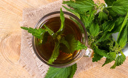 Healing tea with nettle. Tea in a glass cup on a wooden table. The source of vitamins. Stock Images