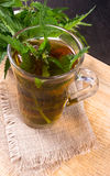 Healing tea with nettle. Tea in a glass cup on a wooden table. The source of vitamins. Royalty Free Stock Images