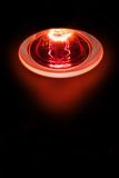 Healing warmth. Close-up picture of the shine of a medicinal red-light-lamp with black background Royalty Free Stock Photography