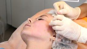 Healtcare-Klinik Junger weiblicher Kunde erhält Threadface lifting-Verfahren Kosmetiker in den Handschuhen, die Gesichtsantialter stock video