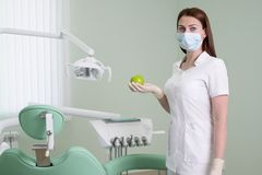 People, medicine, dentistry and healthcare concept - happy young female dentist with green apple in hand on background of medical royalty free stock photo