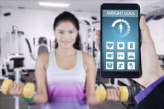 Health app and healthy woman exercising at gym Stock Photo