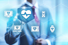 Health applications. Businessman pointing towards camera selecting health application, virtual interface Stock Photography