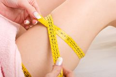 Health and beauty. Close up photo of a woman measuring her leg Royalty Free Stock Images
