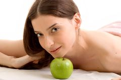 Health and beauty. Beautiful young woman relaxing, with green apple ahead- health and beauty Stock Photography