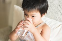 health and beauty concept - Asian little girl holding and drinking a glass of water stock image