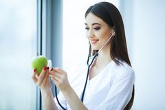Health and Beauty. Doctor Dietitian Standing near the Window at the Light Office. Girl Holds Apple in Hands And Smiles. Doctor Shows Apple royalty free stock images