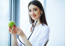 Health and Beauty. Doctor Dietitian Standing near the Window at the Light Office. Girl Holds Apple in Hands And Smiles. Doctor Shows Apple royalty free stock photos